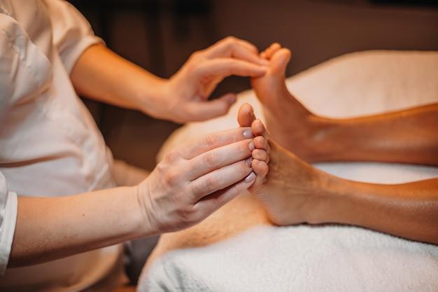 Der junge spa-praktiker massiert die füße des kunden, bevor er mit dem nächsten reinigungsvorgang beginnt