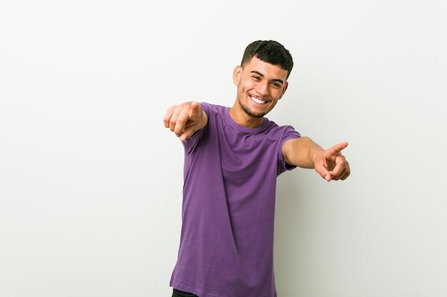 Der junge spanische mann lächelt fröhlich und zeigt nach vorne.