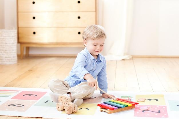 Der junge spielt in einem kindergarten auf dem xylophon. junge spielt mit spielzeug musikinstrument xylophon im kinderzimmer. nahaufnahme eines kindes, das auf xylophon spielt. das konzept der kindlichen entwicklung.