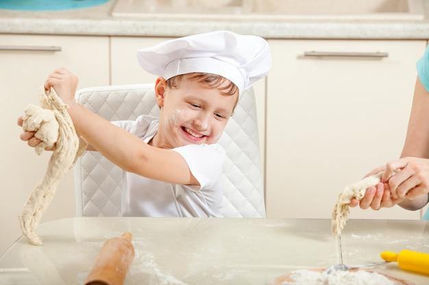 Der junge spielt koch, kocht teigware und bereitet teig zum backen vor. lustiges baby lacht und sagt die küche