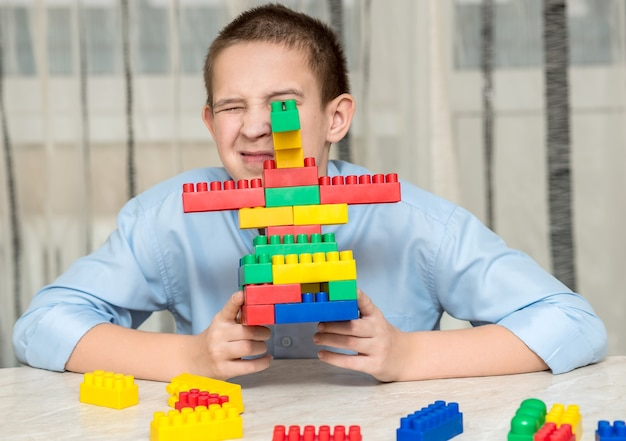 Der junge spielt zu hause auf dem tisch mit plastikwürfeln