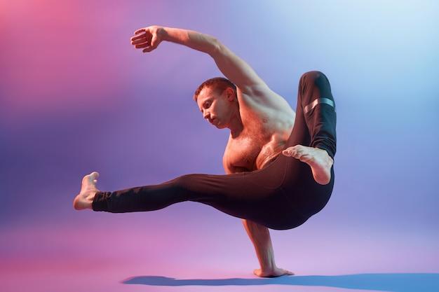Der junge sportler akrobat oder turner, der an der neonwand posiert und seine kraft zeigt, steht auf einer hand, trägt eine schwarze hose und demonstriert seine sportlichen leistungen.