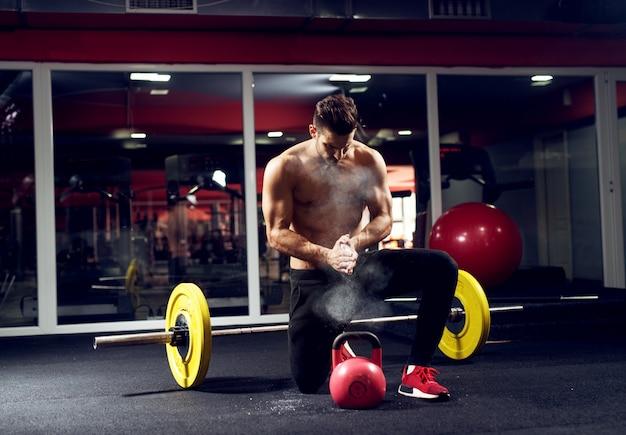 Der junge sportler bereitet sich auf ein training mit der kettlebell im fitnessstudio vor.
