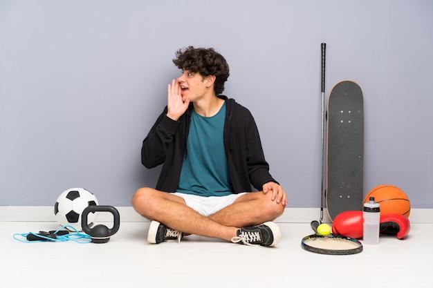 Der junge sportmann, der auf dem boden um viele sportelemente schreit mit dem breiten mund sitzt, öffnen sich