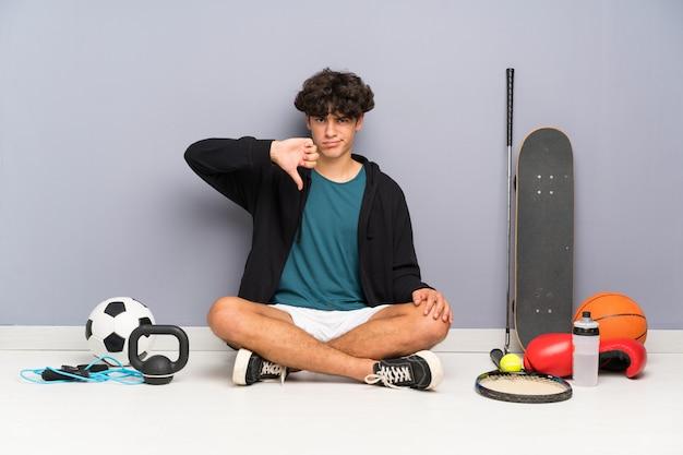 Der junge sportmann, der auf dem boden um viele sportelemente zeigen daumen unterzeichnen sitzt unten