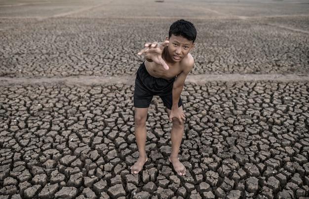 Der junge stand gebeugt auf den knien und machte ein zeichen, um nach regen, globaler erwärmung und wasserkrise zu fragen.