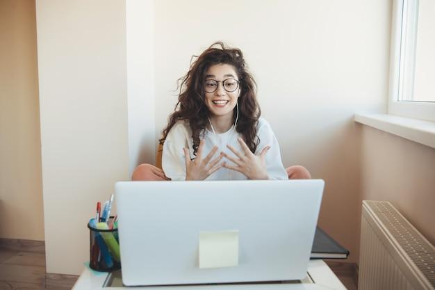 Der junge student mit den lockigen haaren im online-unterricht trägt eine brille und kopfhörer, die sich vor dem laptop ausdrücken