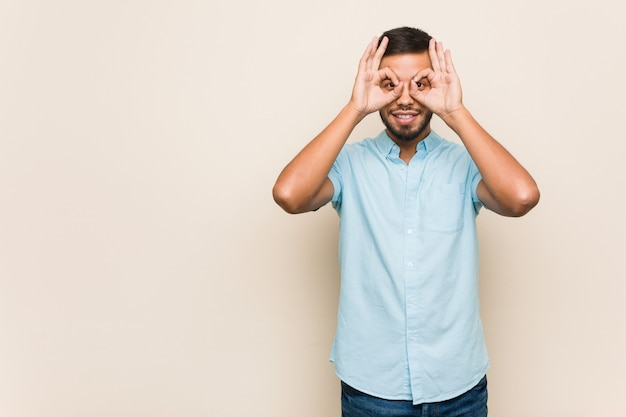 Der junge südasiatische mann, der okay zeigt, unterzeichnen vorbei augen