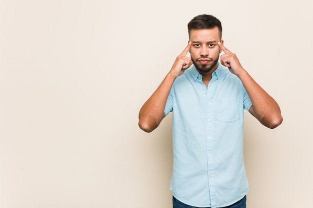 Der junge südasiatische mann konzentrierte sich auf die aufgabe und zeigte mit den zeigefingern auf den kopf.