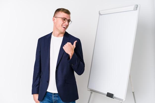 Der junge trainermann, der ein weißes brett zeigt, zeigt mit dem daumenfinger weg, lacht und sorglos.