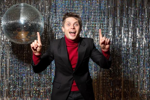 Der junge überraschte blonde mann trägt einen roten rollkragenpullover und jeans im anzug, die auf der party nach oben zeigen