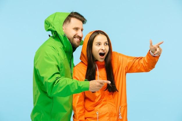 Der junge überraschte couplel posiert in herbstjacken isoliert auf blau