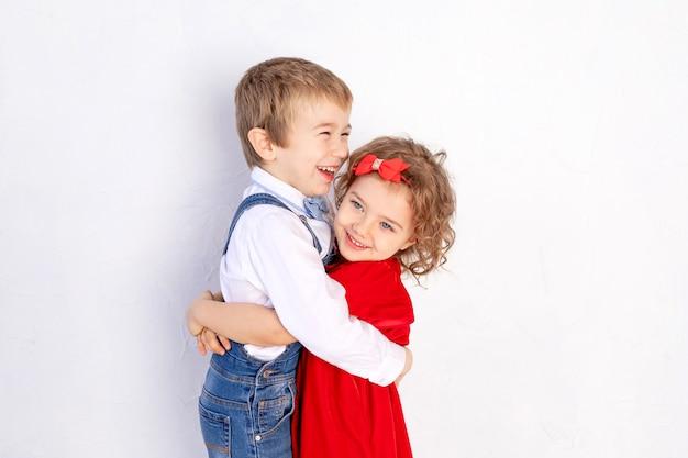 Der junge umarmt das mädchen, das konzept des kindes von freundschaft und liebe