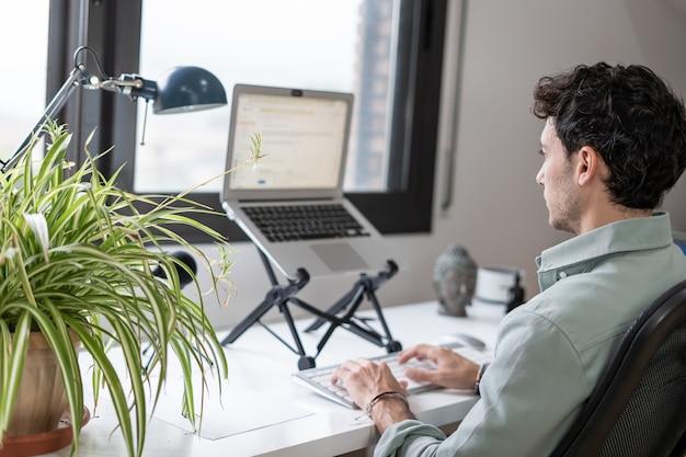 Der junge unternehmer arbeitet von zu hause aus in seinem büro mit dem computer vor einem fenster