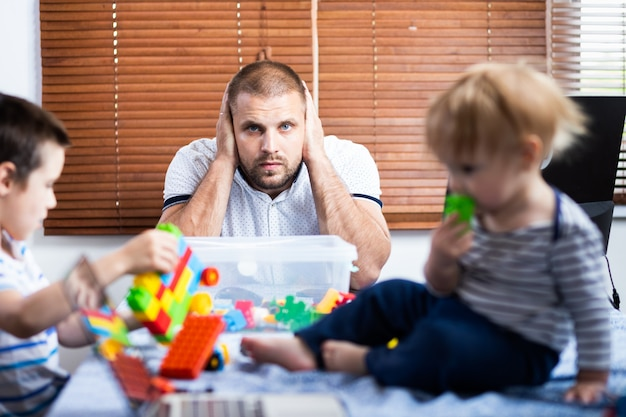 Der junge vater hielt sich die ohren vor lauten schreien zu, die von den söhnen ihrer kinder während der arbeit zu hause unterbrochen wurden
