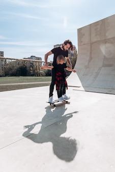 Der junge vater hilft seinem kleinen sohn, am sonnigen tag in einem skatepark auf dem skateboard zu fahren.