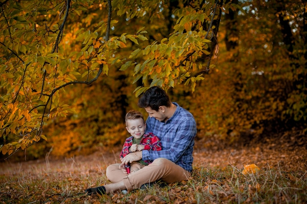 Der junge vater und sein kleiner sohn genießen draußen in einem park