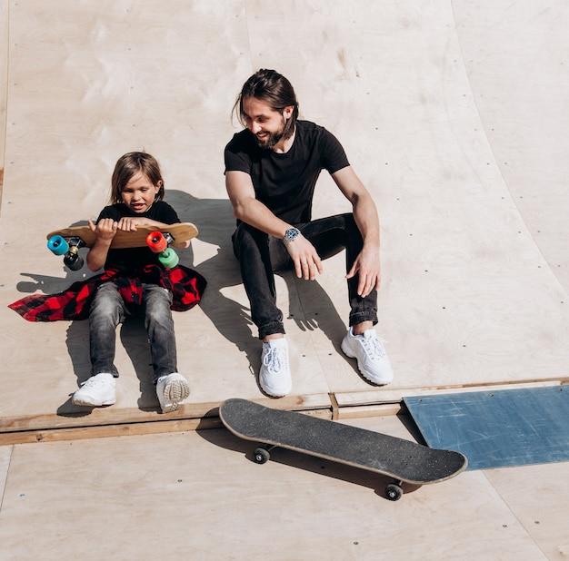 Der junge vater und sein sohn in der stylischen freizeitkleidung sitzen am sonnigen warmen tag zusammen auf der rutsche neben den skateboards in einem skatepark.