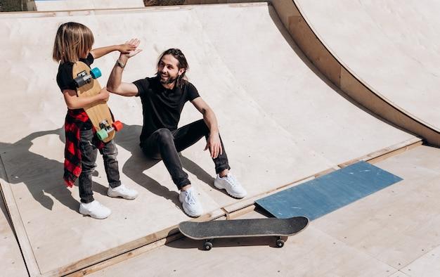 Der junge vater und sein sohn in der stylischen freizeitkleidung sitzen und amüsieren sich am sonnigen warmen tag zusammen auf der rutsche neben den skateboards in einem skatepark.