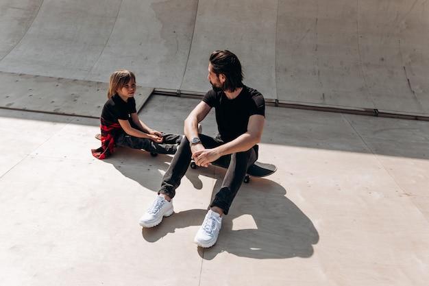 Der junge vater und sein sohn in freizeitkleidung sitzen am sonnigen tag auf den skateboards in einem skatepark.