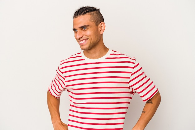 Der junge venezolanische mann isoliert auf weißem hintergrund lacht und schließt die augen, fühlt sich entspannt und glücklich.