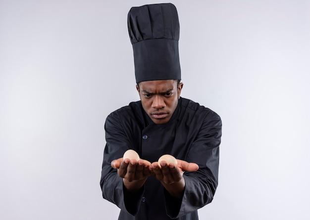 Der junge verwirrte afroamerikanische koch in der kochuniform hält und betrachtet eier, die auf weißer wand isoliert werden