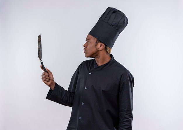Der junge verwirrte afroamerikanische koch in der kochuniform steht seitlich und hält das braten panisoliert auf der weißen wand