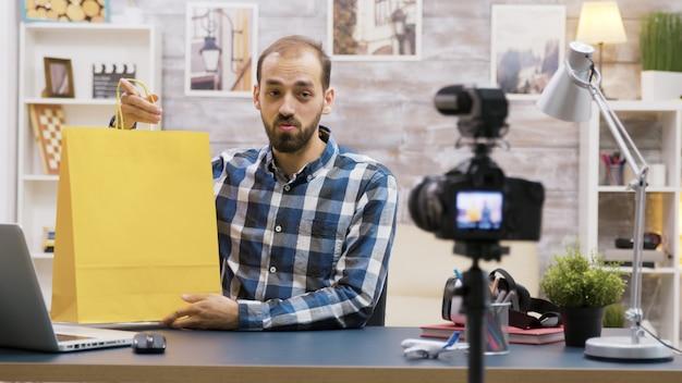 Der junge vlogger präsentiert seinen followern ein besonderes giveaway. berühmte influencer. kreativer inhaltsersteller.
