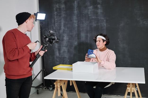 Der junge vlogger zeigt seinem freund neue schuhe mit einer videokamera, die vor ihm steht und ihn im studio fotografiert
