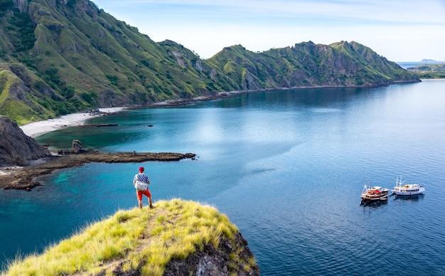 Der junge wanderer, der allein auf klippen-berg steht, genießen die ansicht von padar island vor sonnenuntergang