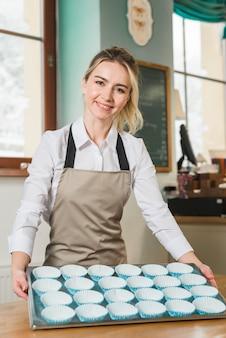 Der junge weibliche bäcker, der backblech zeigt, füllte mit einem leeren blauen kasten des kleinen kuchens