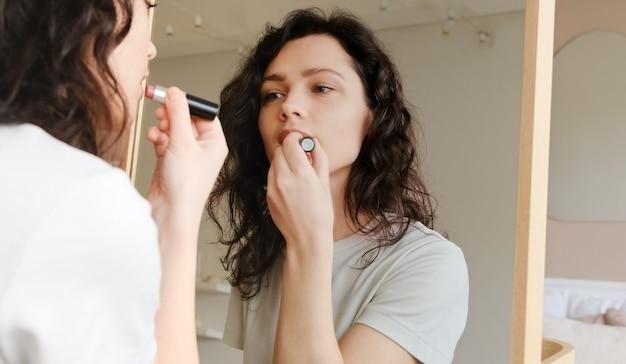 Der junge weibliche haltene lippenstift in ihren händen und in farbenlippen bereiten morgens fertig werden vor. frau make-up zu tun. mach dich bereit für ein date.