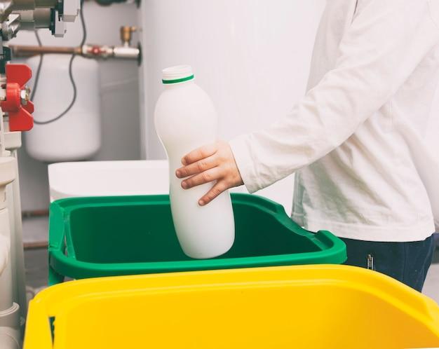 Der junge wirft die leere plastikflasche in einen von drei mülleimern