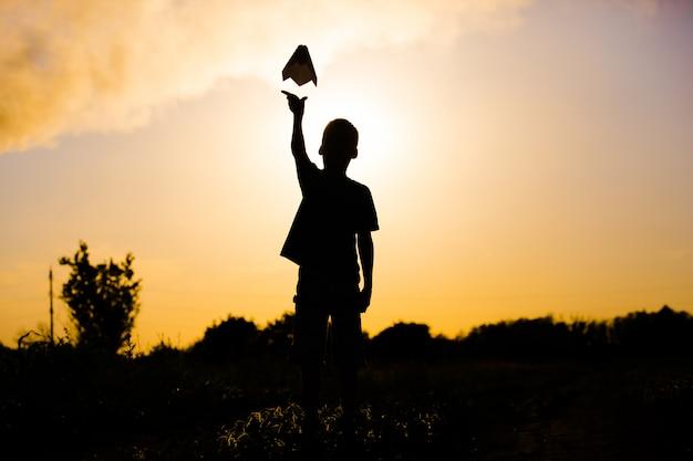 Der junge wirft ein papierflugzeug vor den hintergrund einer pfeife. ökologie.