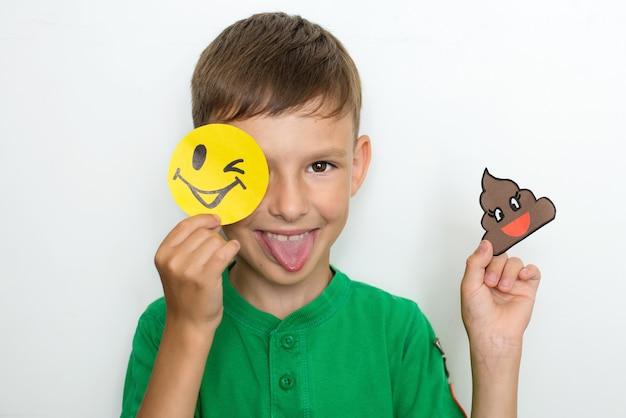 Der junge zeigt emotionen und hält ein lustiges lächeln aus papier