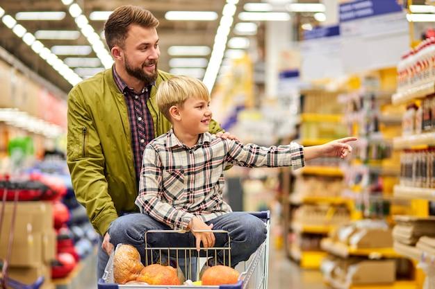 Der junge zeigt mit dem finger auf die seite im laden und zeigt dem vater etwas. er möchte, dass der vater etwas auf dem lebensmittelmarkt kauft und auf dem wagen sitzt