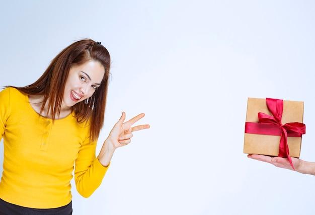 Der jungen frau im gelben hemd wird eine geschenkbox aus karton mit rotem band und positivem handzeichen angeboten