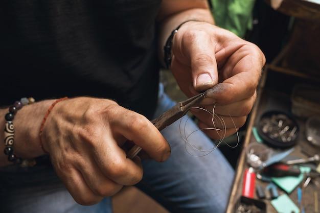 Der juwelier macht eine feder aus draht für ein schloss zu einem goldprodukt