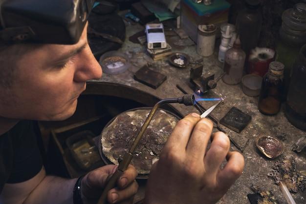 Der juwelier schmilzt das goldstück zur weiteren reparatur