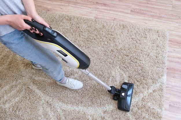 Der kabellose staubsauger wird verwendet, um den teppich im raum zu reinigen. hausarbeit mit einem neuen handstaubsauger. hausreinigung, pflege und technologiekonzept.