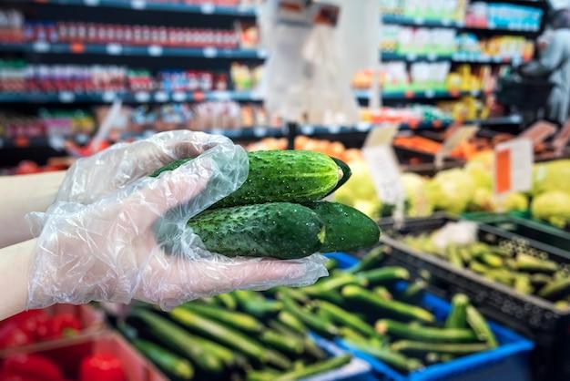 Der käufer in handschuhen wählt gemüse während einer pandemie aufgrund eines neuen gefährlichen virus, dem coronavirus