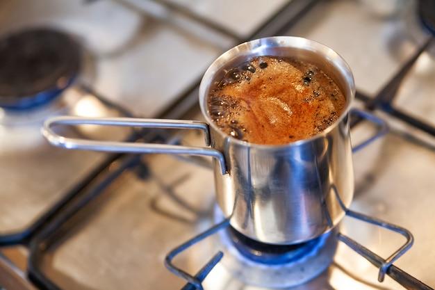 Der kaffee wird in einem cezve auf einem gasherd gebrüht.