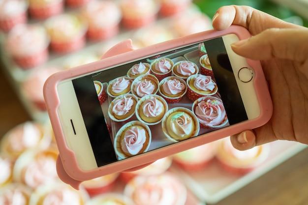 Der kaffeehausbesitzer fotografiert mit einem smartphone frisch gebackene cupcakes, um sie auf online-medien und websites zu bewerben. produkte online verkaufen