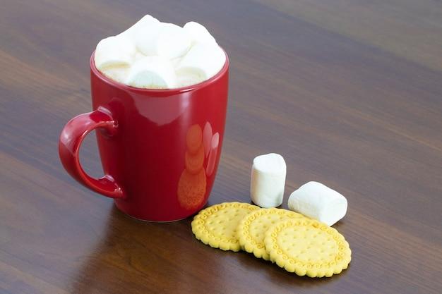 Der kakao im roten becher mit marshmallows auf dem holztisch