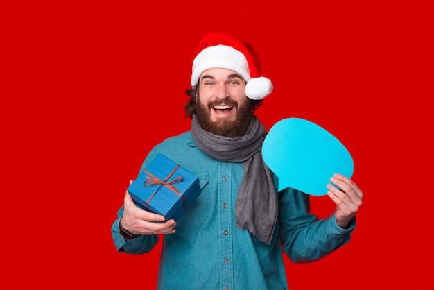 Der kameramann anlächelnd hält eine geschenkbox und eine blaue sprechblase.