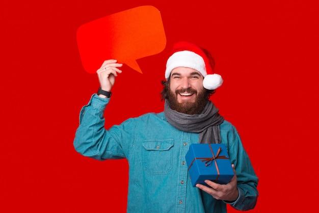 Der kameramann anlächelnd hält eine geschenkbox und eine rote sprechblase.