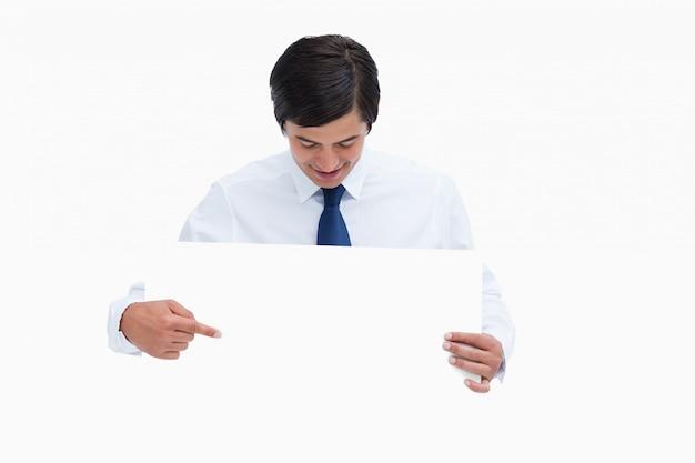Der kaufmann, der leeres zeichen in seinen händen zeigt und betrachtet