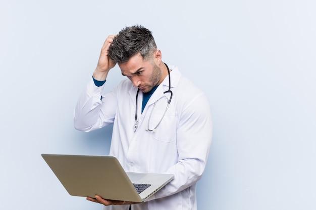 Der kaukasische doktormann, der einen laptop entsetzt hält, hat sich an wichtige sitzung erinnert.