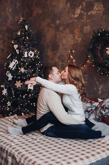 Der kaukasische ehemann und die kaukasische ehefrau entspannen sich auf einem gemütlichen bett neben dem großen weihnachtsbaum