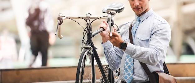 Der kaukasische geschäftsmann arbeitet mit dem fahrrad am autofreien tag in der stadt - urbaner lebensstil